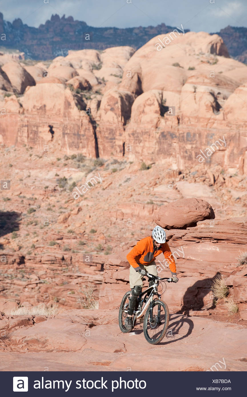 A young man rides across the slickrock on the Amasa Back Trail in Moab, UT. - Stock Image