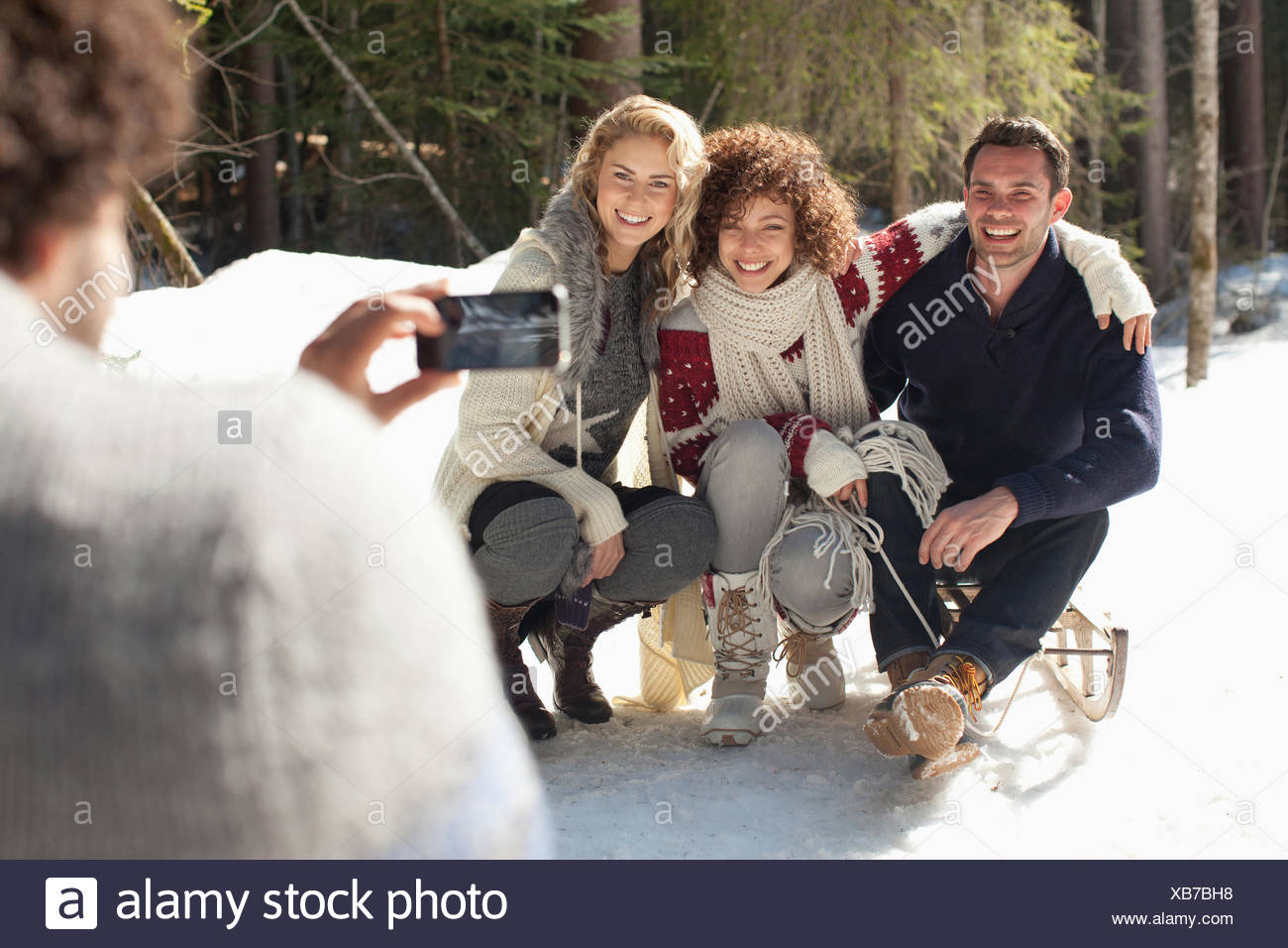 Man photographing friends with sled - Stock Image