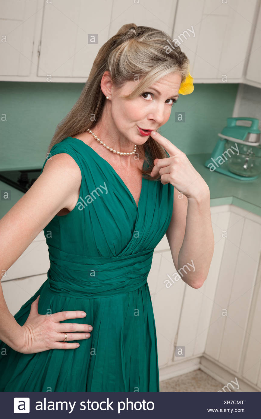 Beautiful Caucasian housewife in kitchen with index finger on lips ...