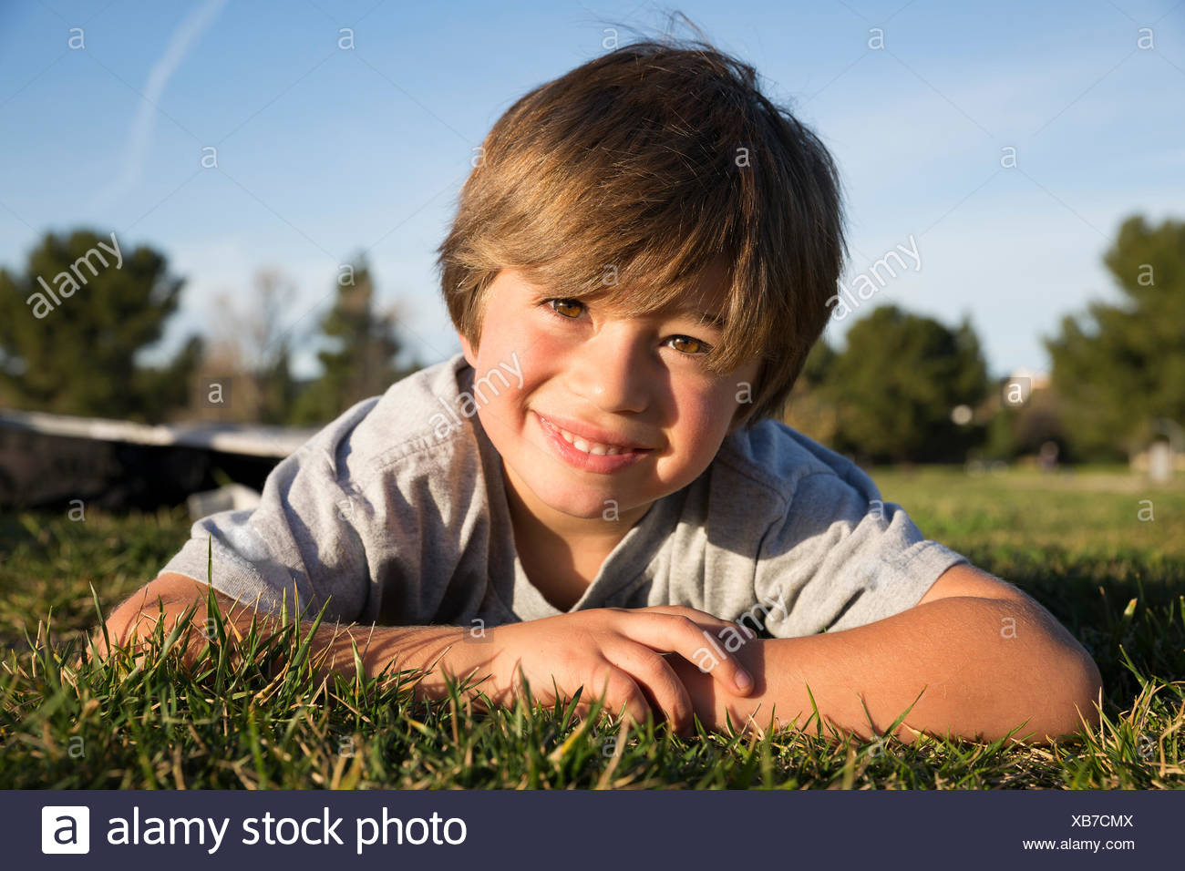 Portrait of smiling boy lying on park grass - Stock Image