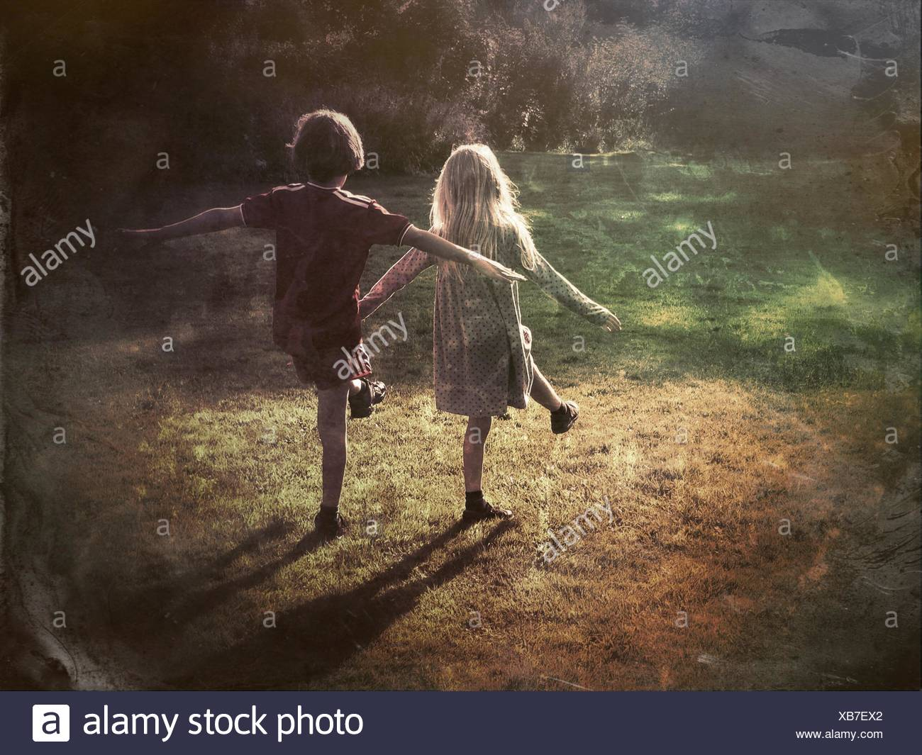 Rear View Of Siblings Playing On Ground - Stock Image