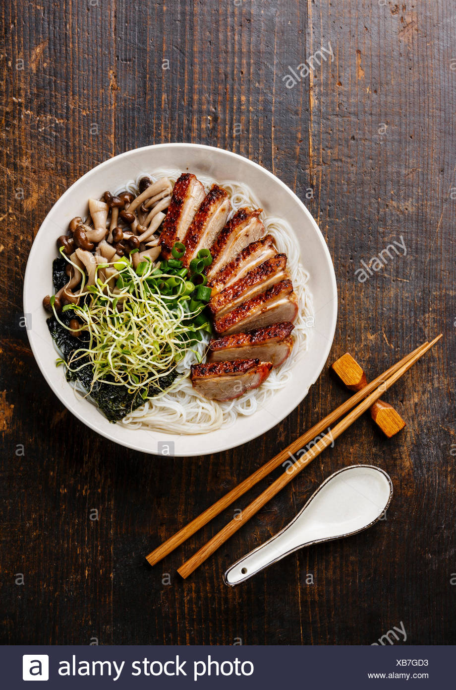 Rice noodles bowl with Peking Duck and mushrooms on wooden background - Stock Image