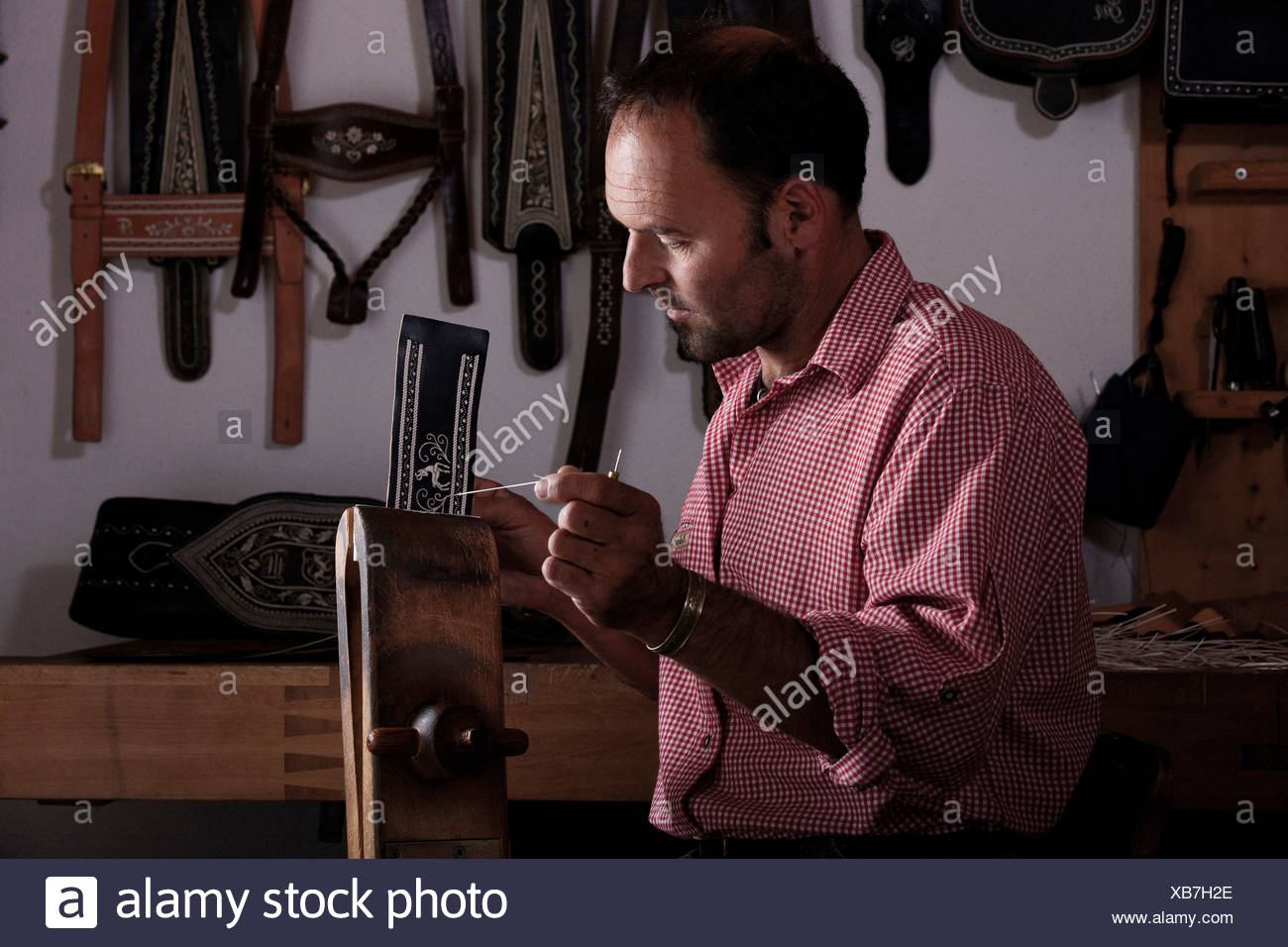 Male, 35-40 years, doing pinfeather embroidery, Reith im Alpbach, Tyrol, Austria - Stock Image