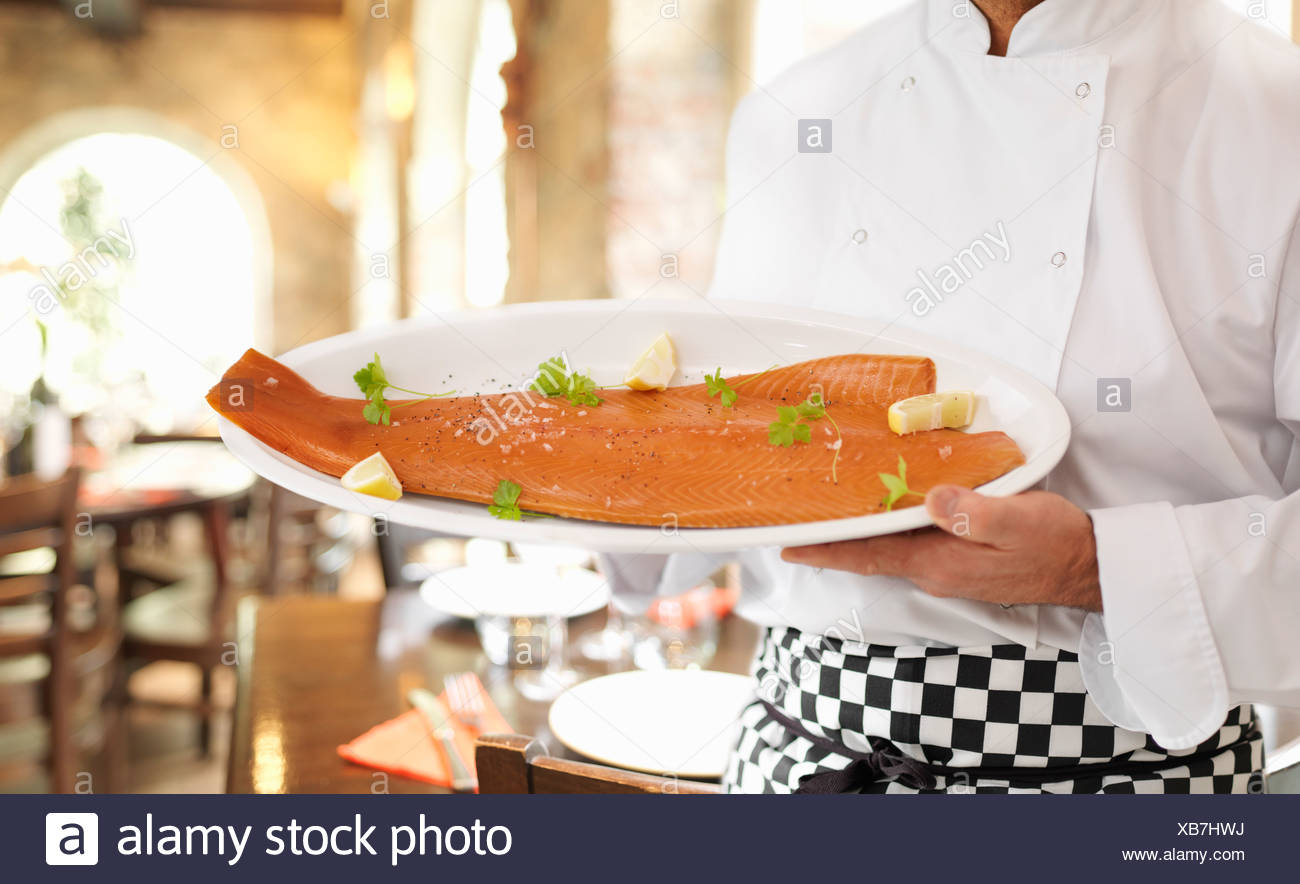 Chef holding plate of salmon - Stock Image