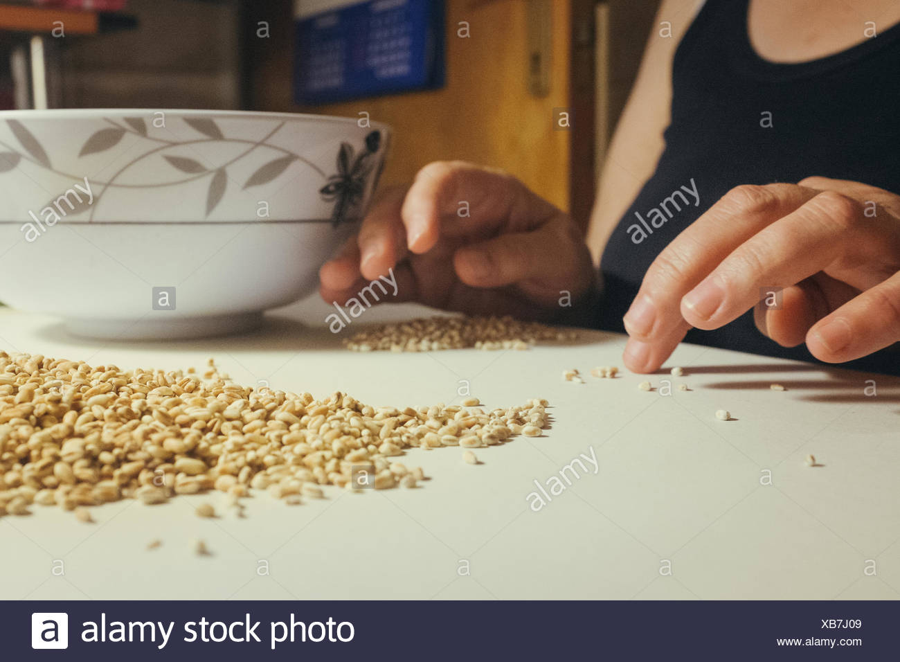 Woman Separating Stones From Grains On Table - Stock Image