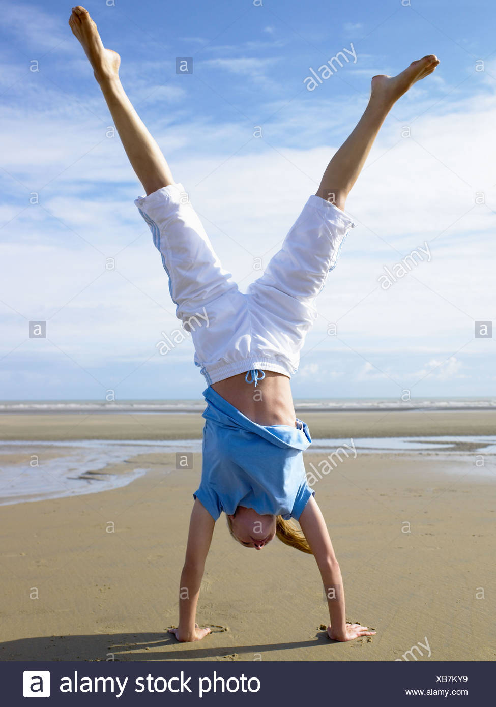 Woman doing a handstand on the beach - Stock Image