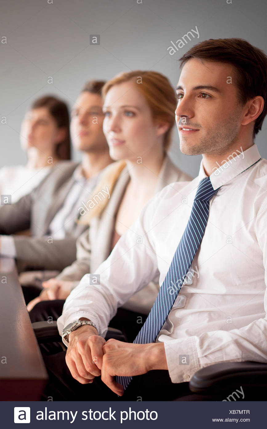 Young business professionals attending conference - Stock Image