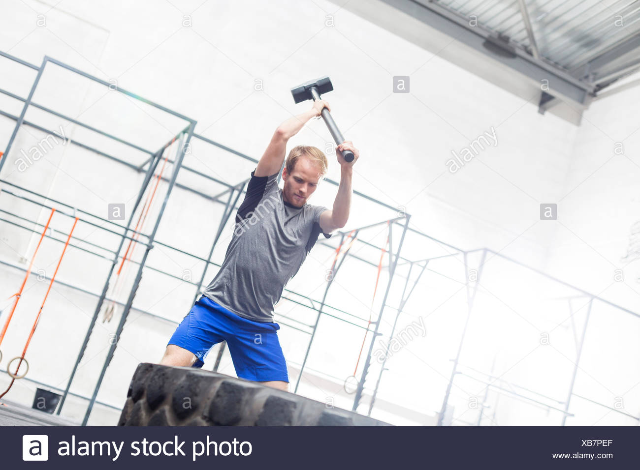 Man hitting tire with sledgehammer in crossfit gym - Stock Image