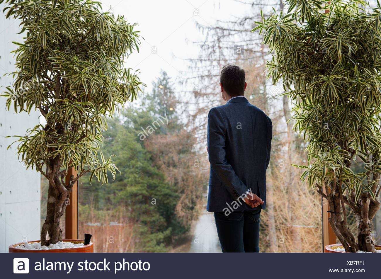 Man looking through glass wall - Stock Image