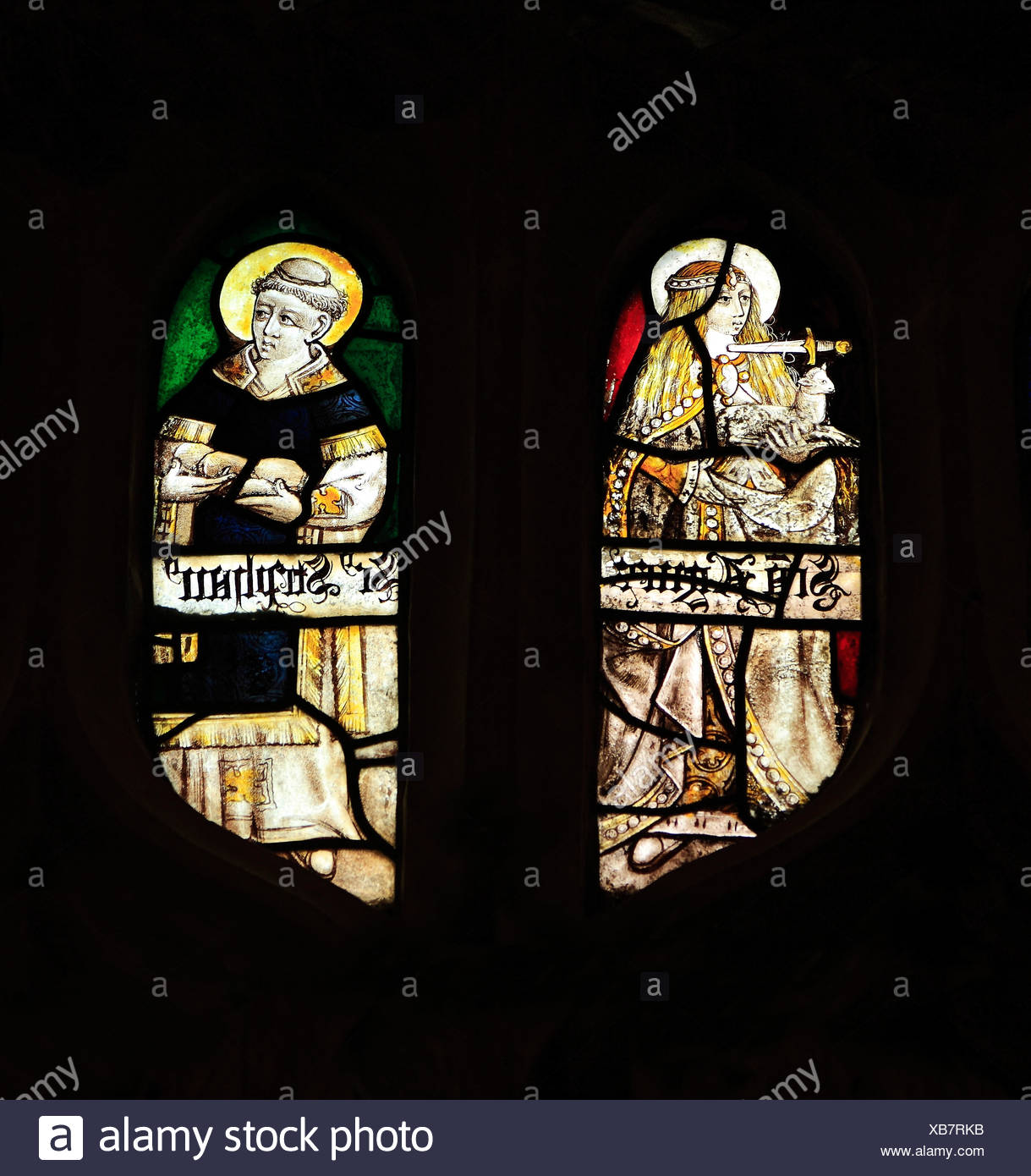Medieval stained glass, St. Agnes with dagger at her neck, holding a lamb, St. Stephen holding stones of martyrdom, Sandringham - Stock Image