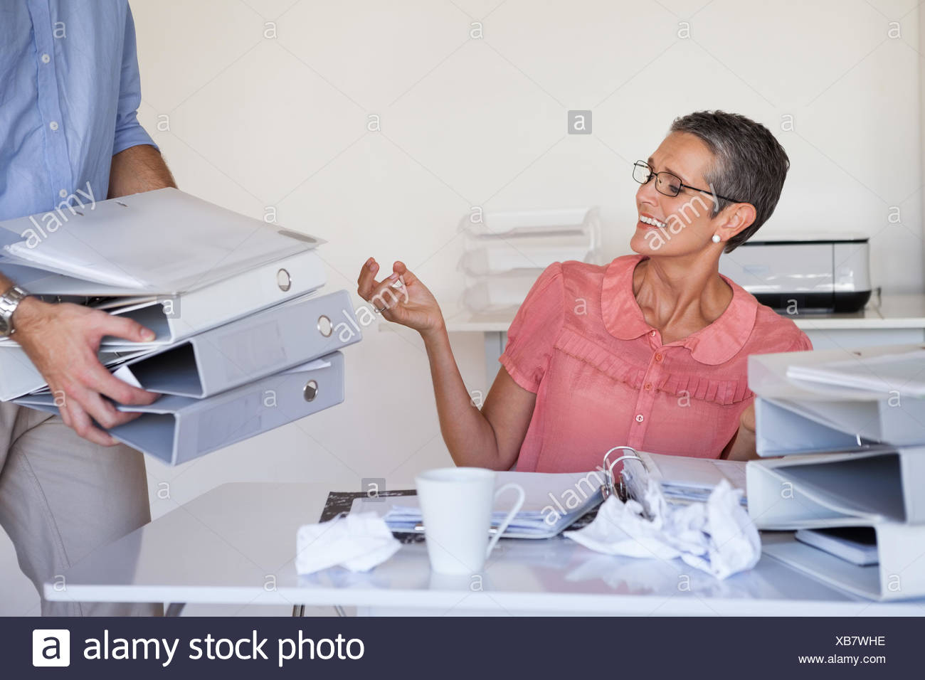Casual businesswomans workload getting bigger and bigger - Stock Image