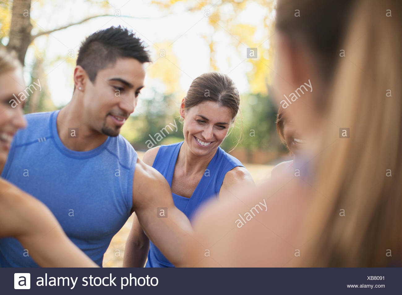 Fitness class doing hand over hand cheer after workout. - Stock Image