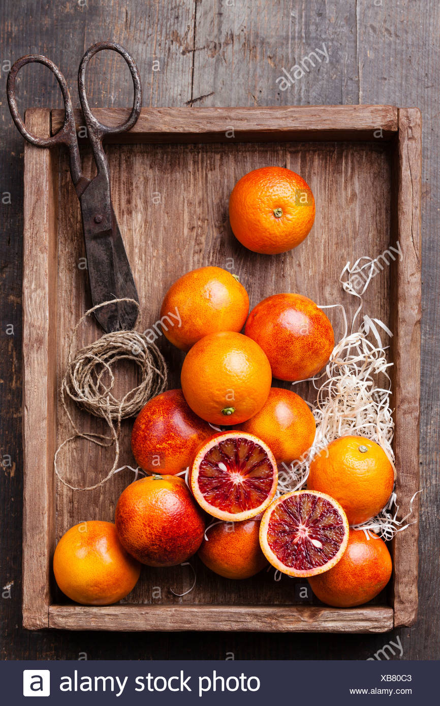 Ripe red oranges on textured wooden background - Stock Image