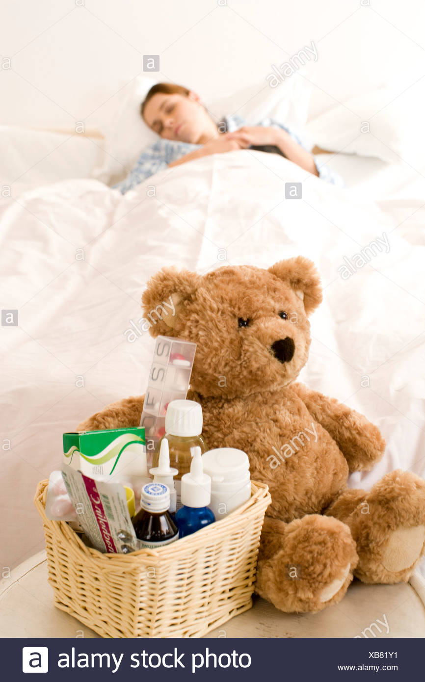 Sick woman laying in bed - Stock Image