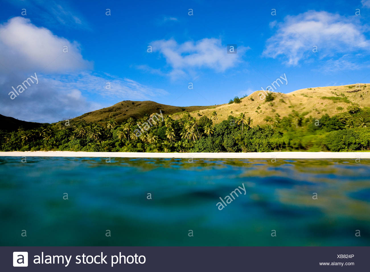 Clouds pass over the rolling hills of the island of Nacula, Fiji. - Stock Image