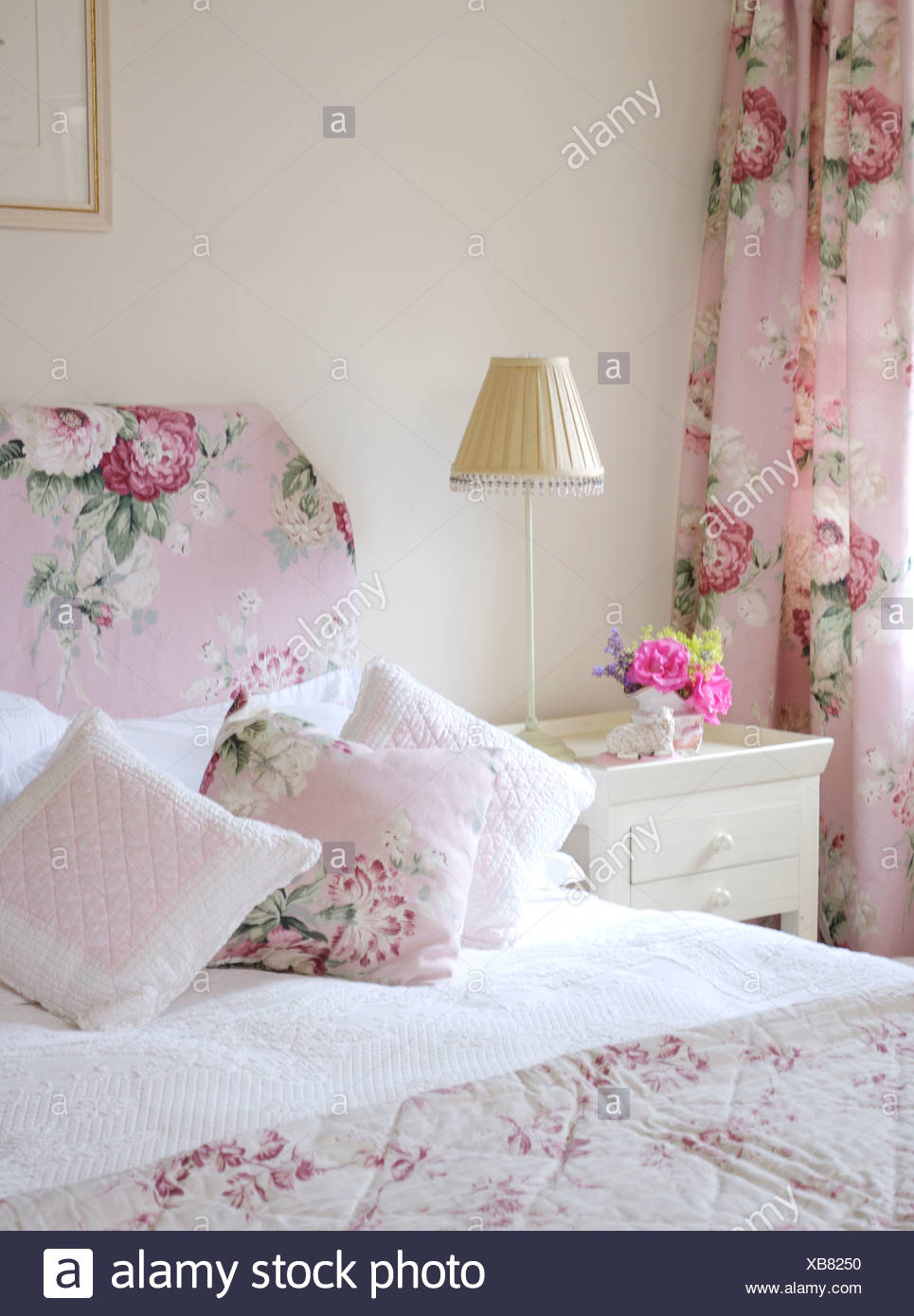 Bed with rose patterned headboard and coordinating cushions ...