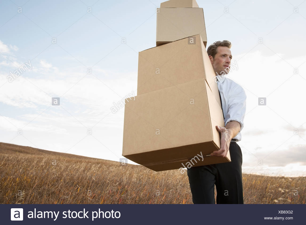 Businessman carrying stacked boxes on field - Stock Image