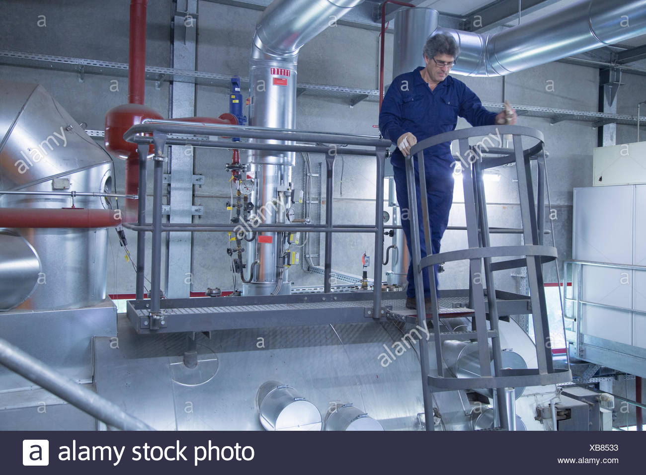 Engineer inspecting on stairs of access platform in power station - Stock Image