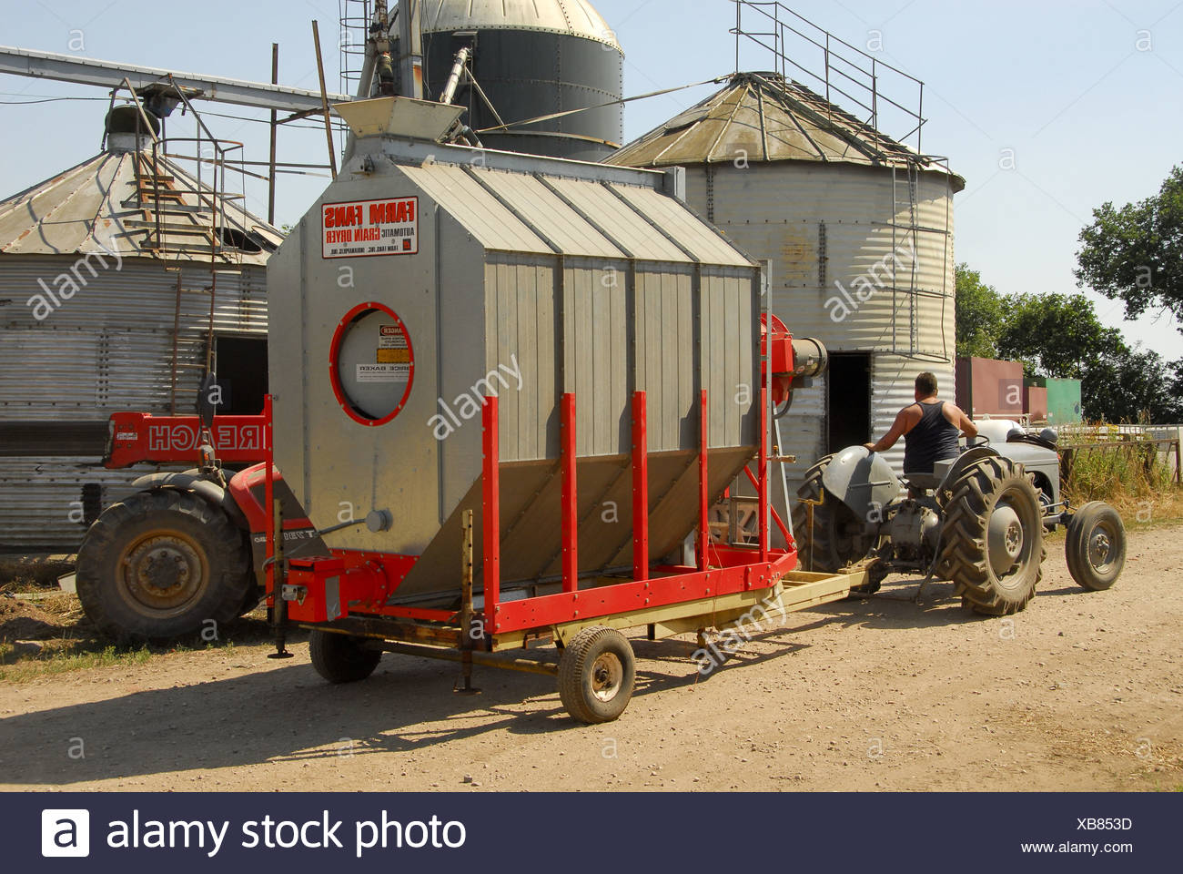 Mobile grain dryer being moved by tractor - Stock Image
