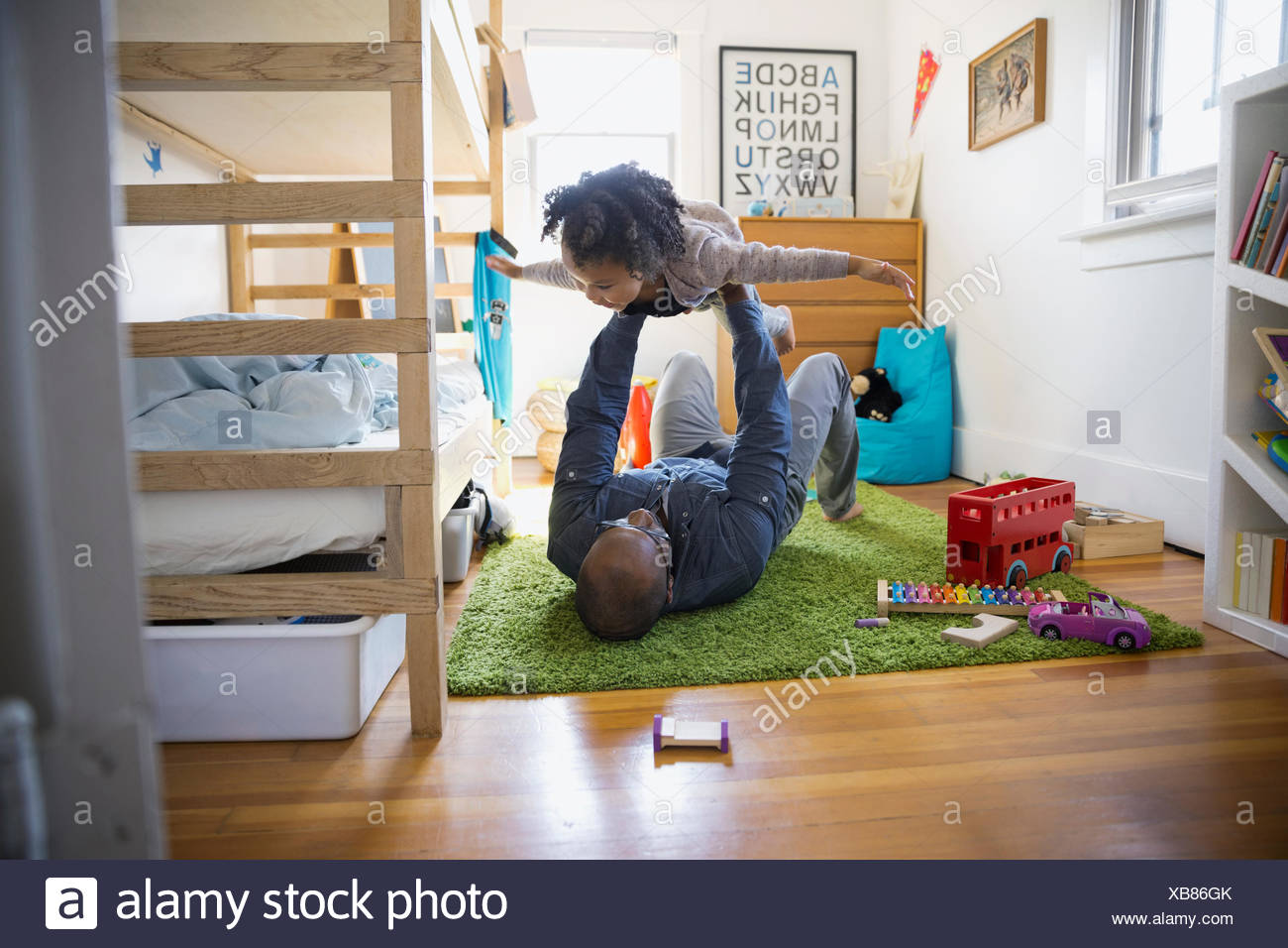 Father lifting flying daughter in bedroom - Stock Image