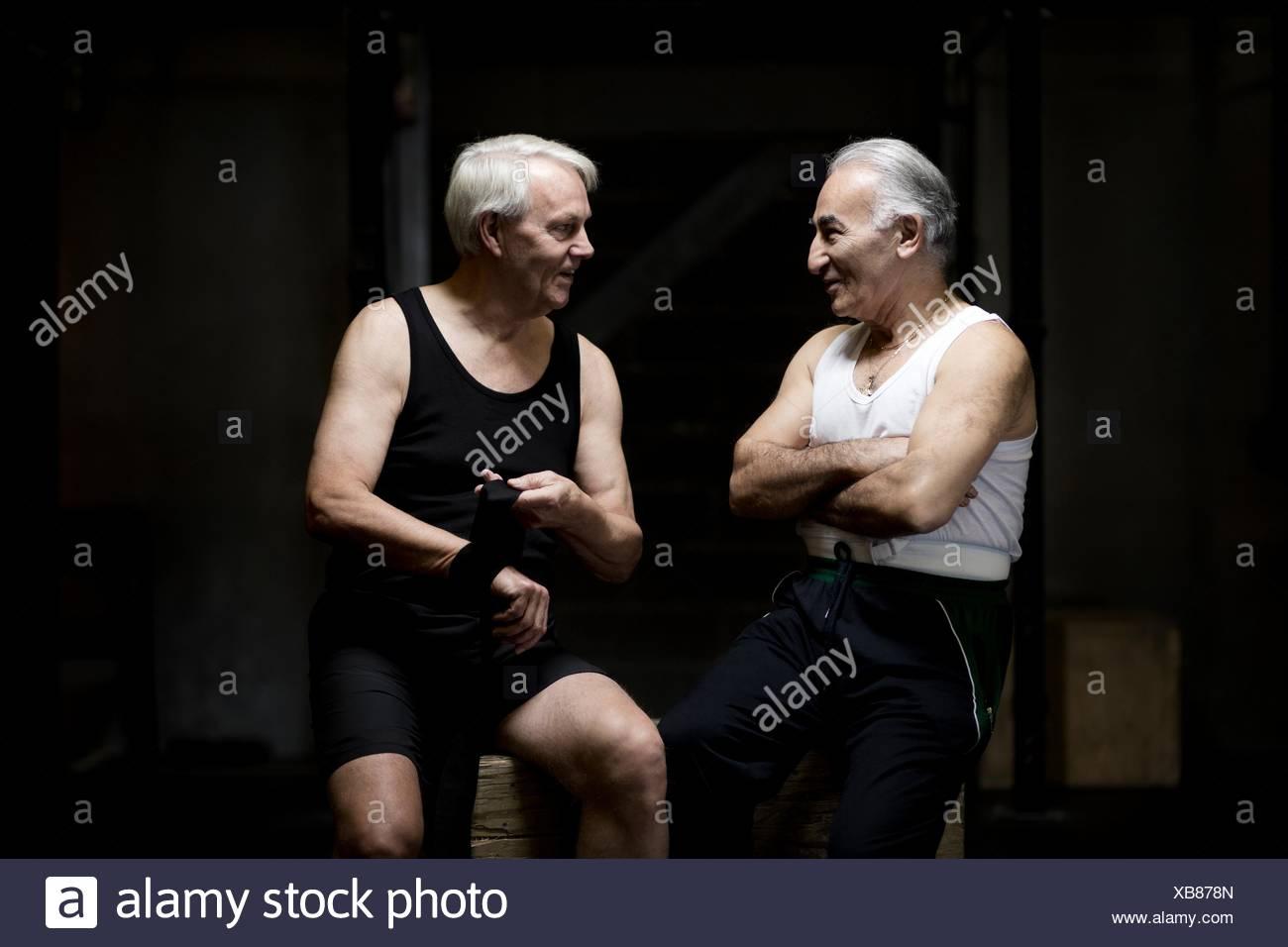 Two senior men chatting and preparing in dark gym - Stock Image