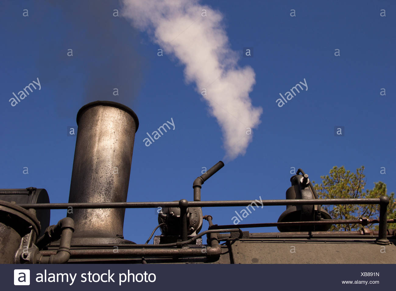 Escaping steam whispers from a steam locomotive ready to go. - Stock Image