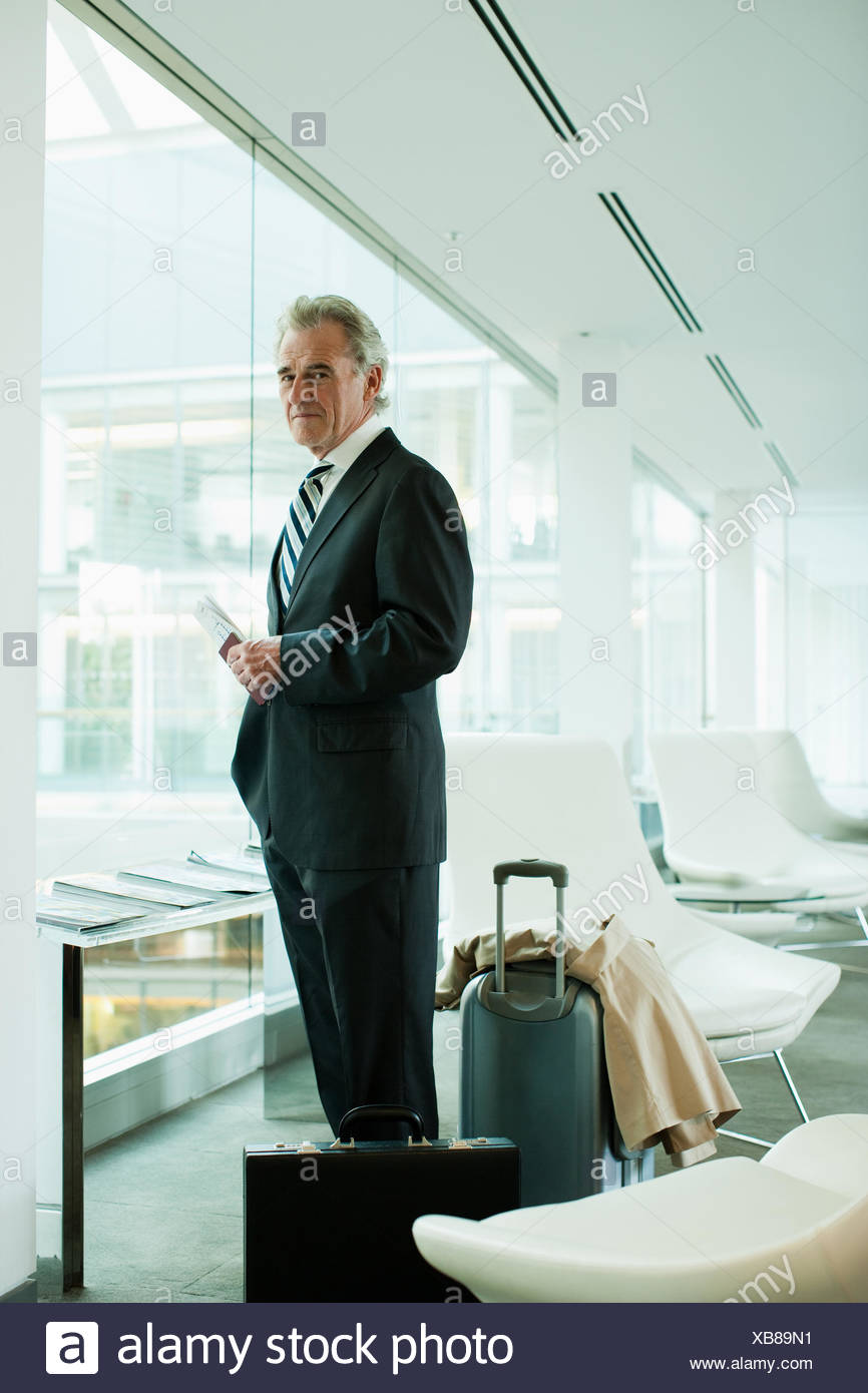 Businessman standing with passport and luggage in airport - Stock Image