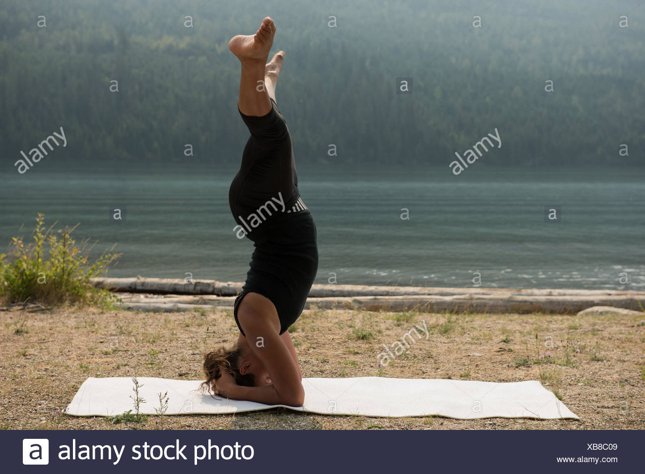 Sporty woman practicing head stand near the sea coast - Stock Image