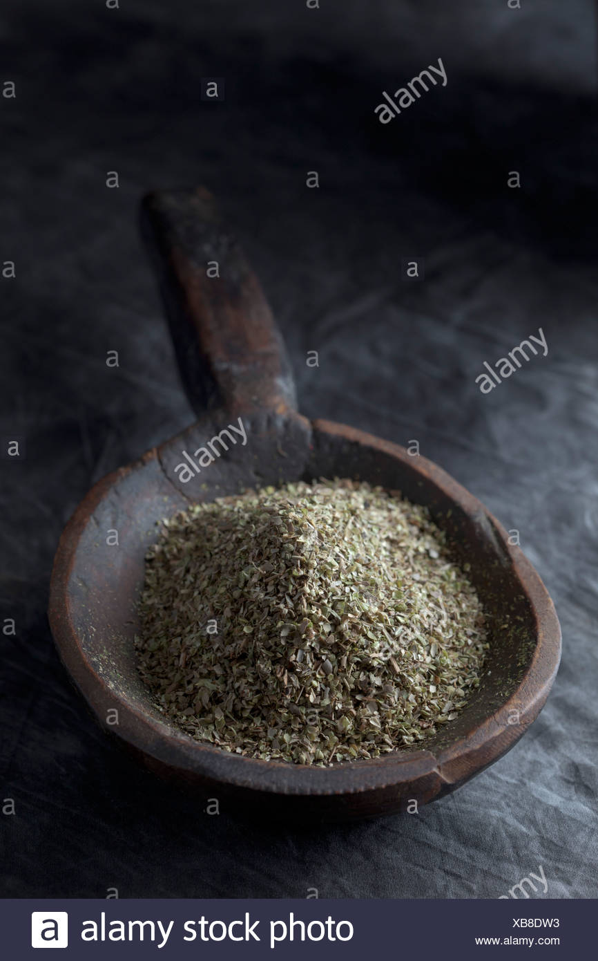 Grained oregano in wooden spoon, close up - Stock Image
