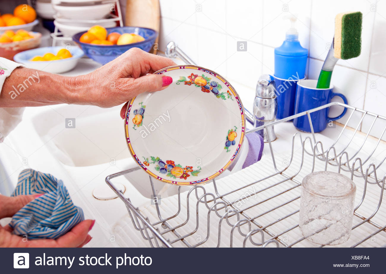 Cropped image of senior woman arranging plate in rack at kitchen counter Stock Photo