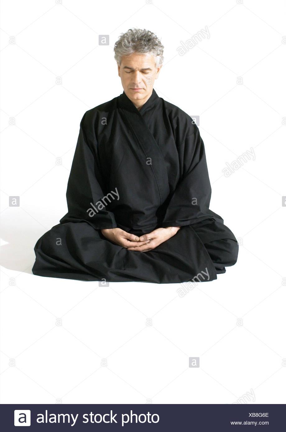 Man sitting on floor, meditating - Stock Image