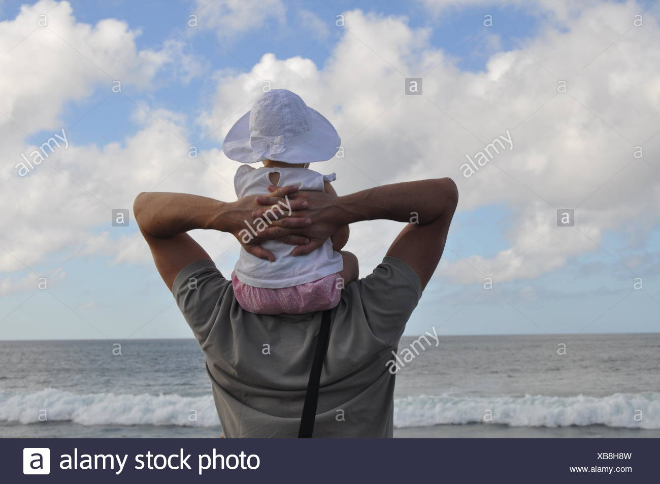 Rear View Of Father Piggybacking Baby Girl At Beach Against Sky - Stock Image