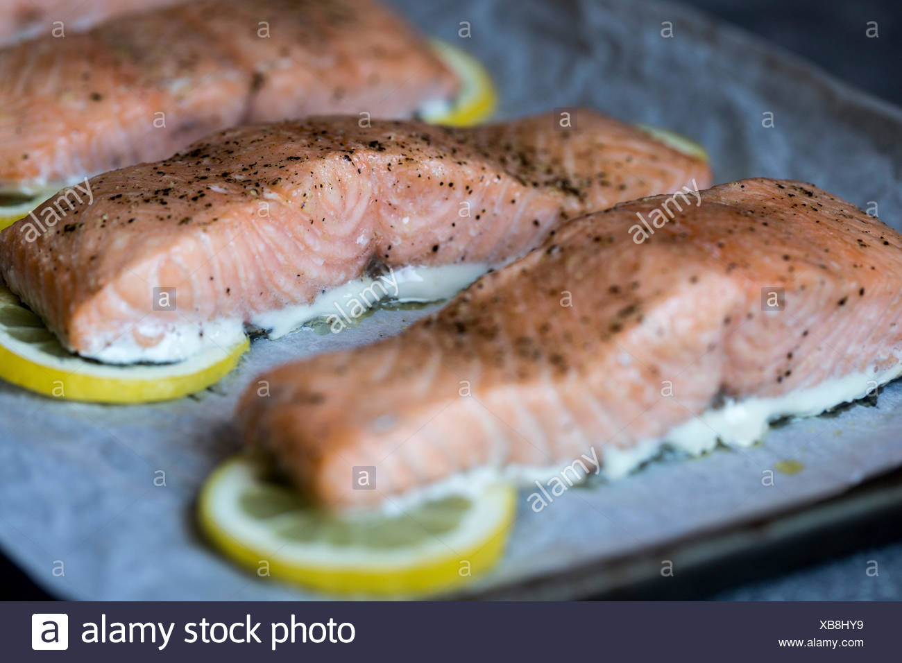 Slow-baked salmon slices are photographed right after they came out of the oven. - Stock Image