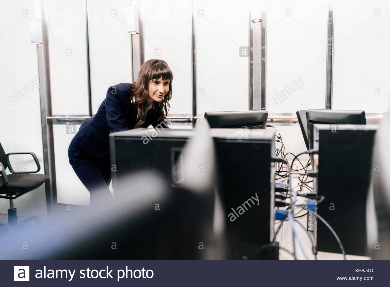 Successful businesswoman looking at monitors in office - Stock Image