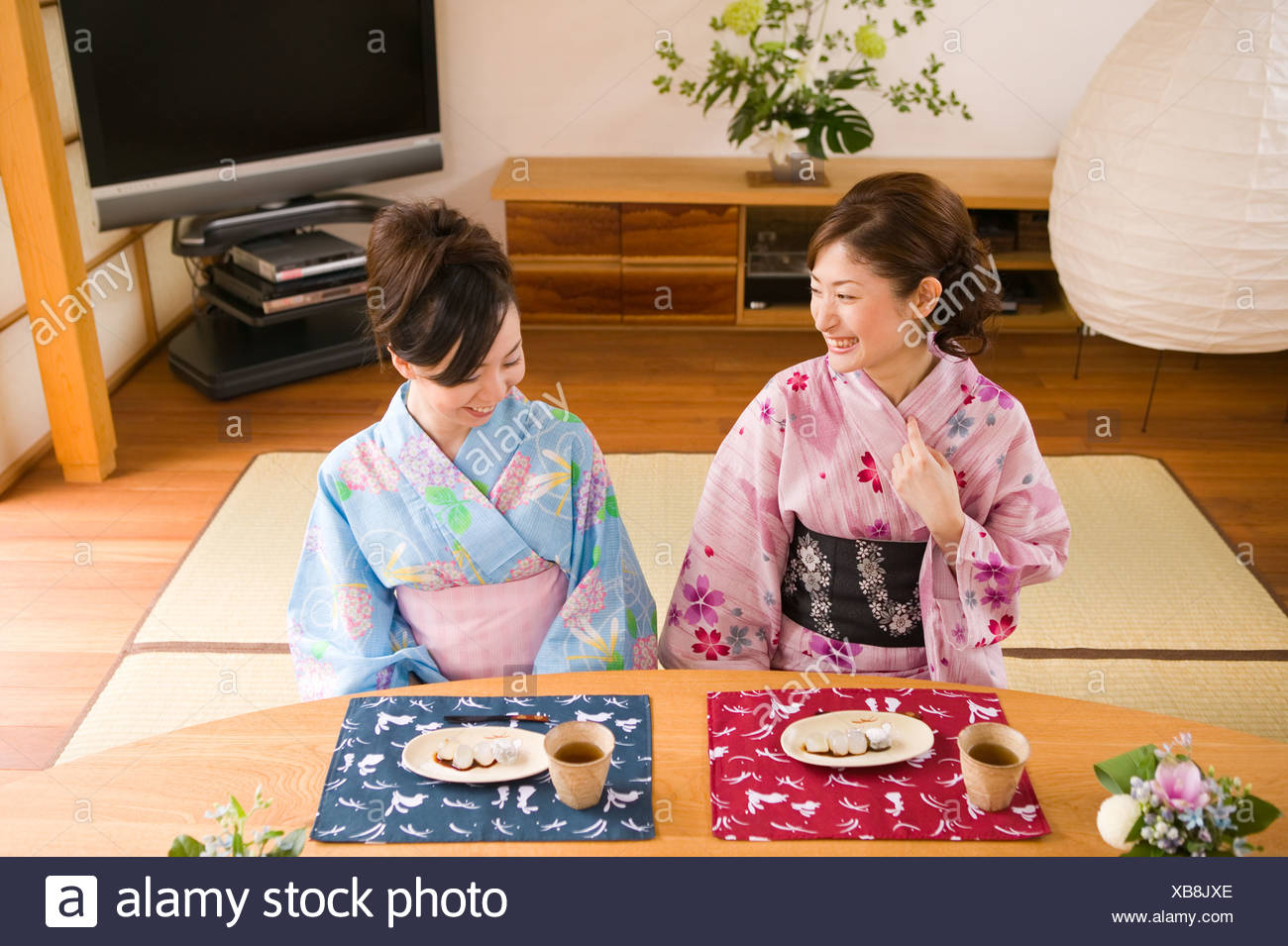 Two young women wearing yukata sitting Stock Photo