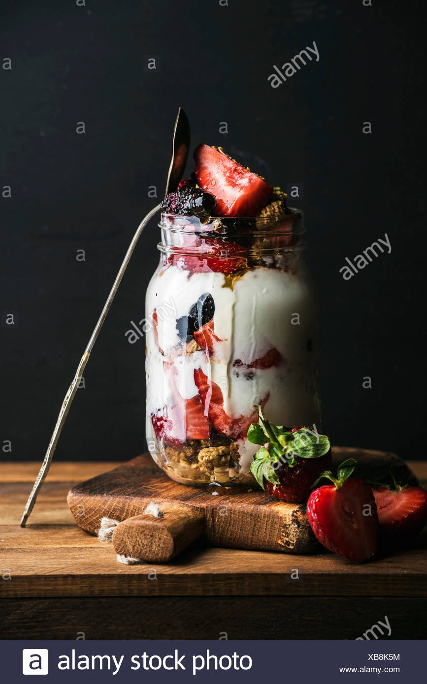 Yogurt oat granola with strawberries, mulberries, honey and mint leaves in tall glass jar on black backdrop - Stock Image