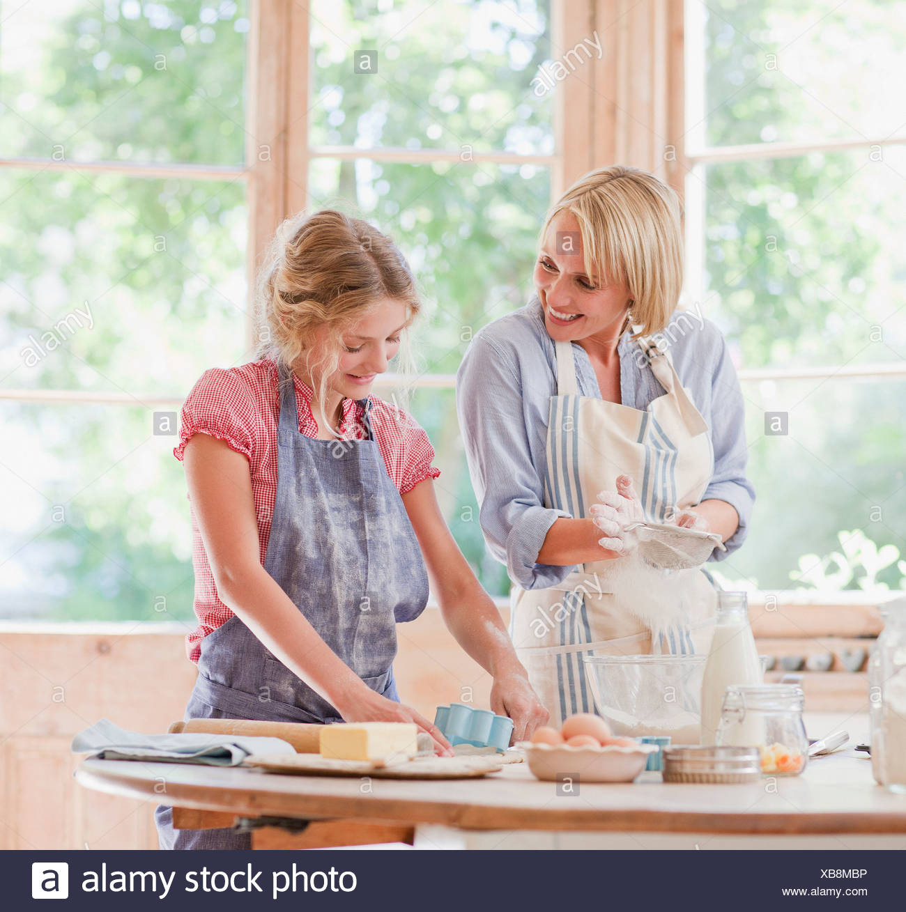 Mother and daughter baking at table in kitchen - Stock Image