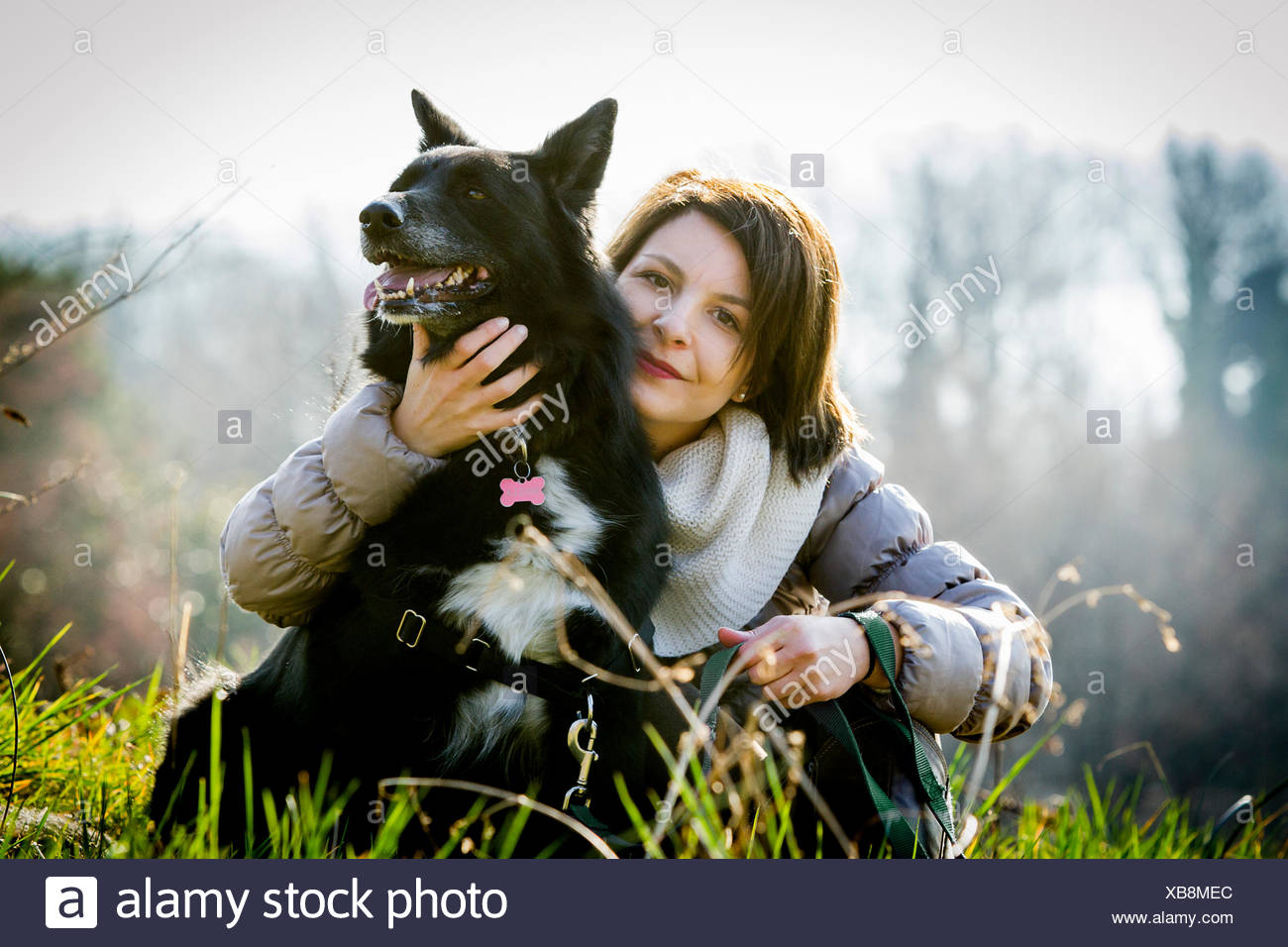 Portrait of mid adult woman with arm around her dog in field - Stock Image