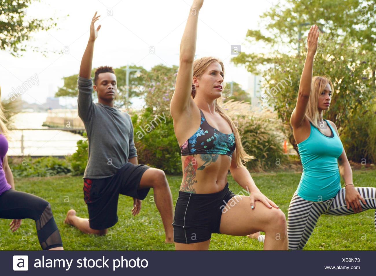 Men and women practicing yoga pose on one knee in park - Stock Image