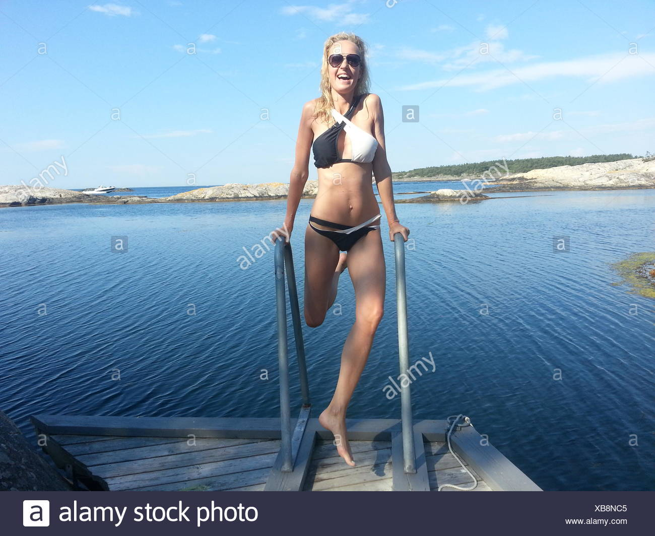 Woman messing about on jetty by fjord, Norway - Stock Image