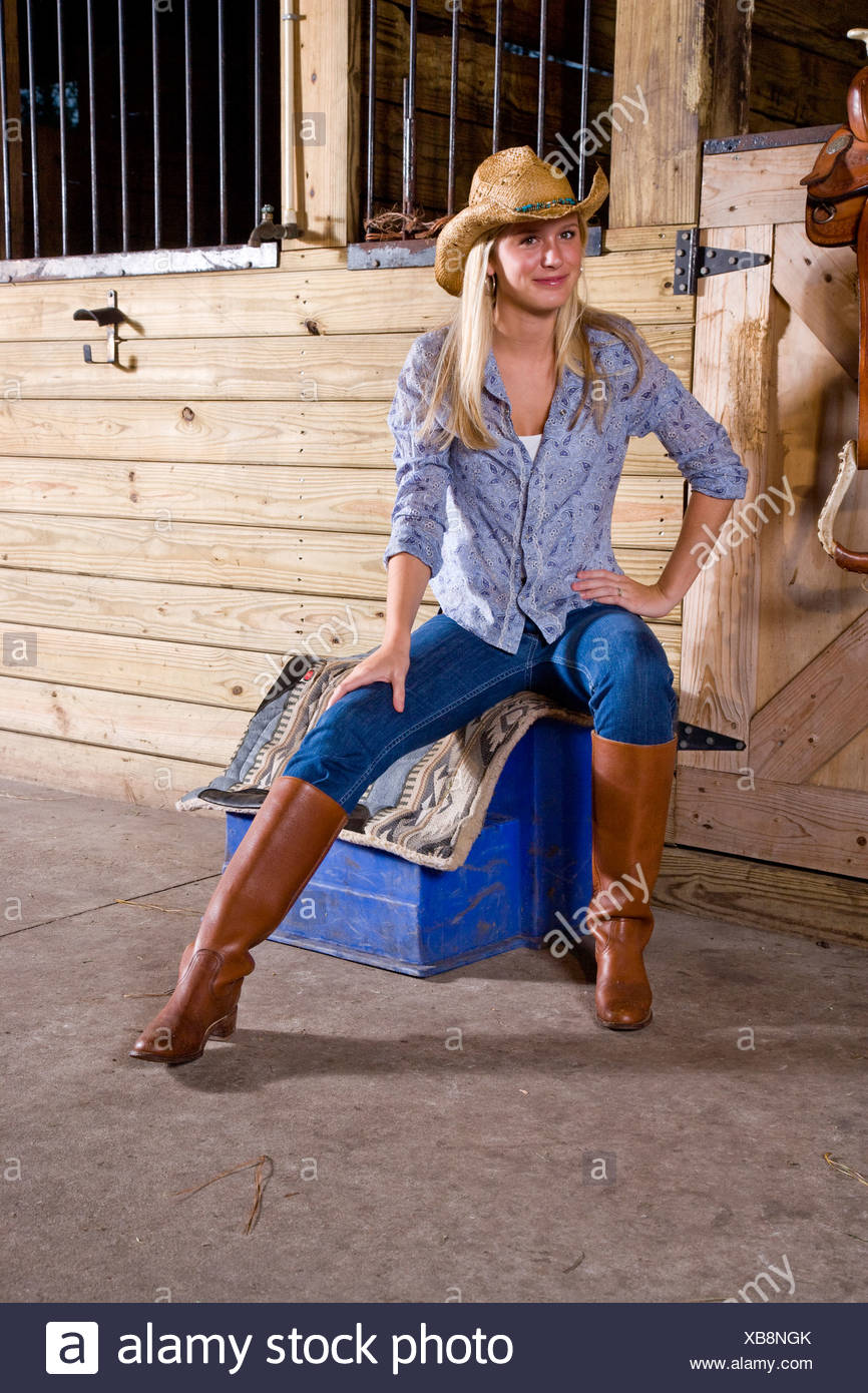Teenage girl in stable with saddle wearing cowboy hat and boots - Stock  Image 42ab43370df1