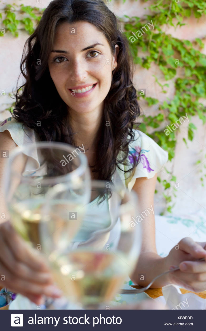 Woman clinking glasses - Stock Image