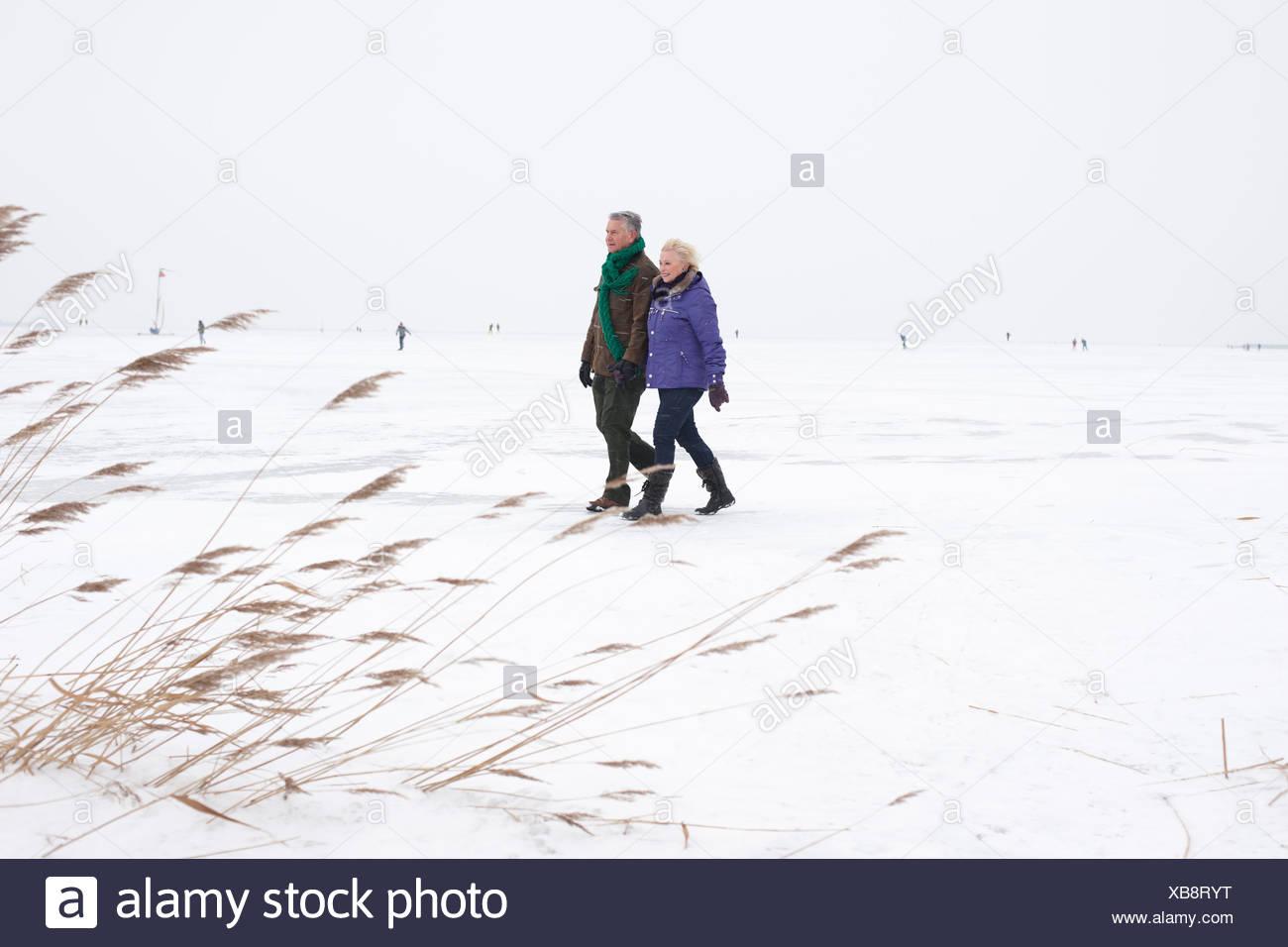 Senior couple walking together on frozen lake - Stock Image