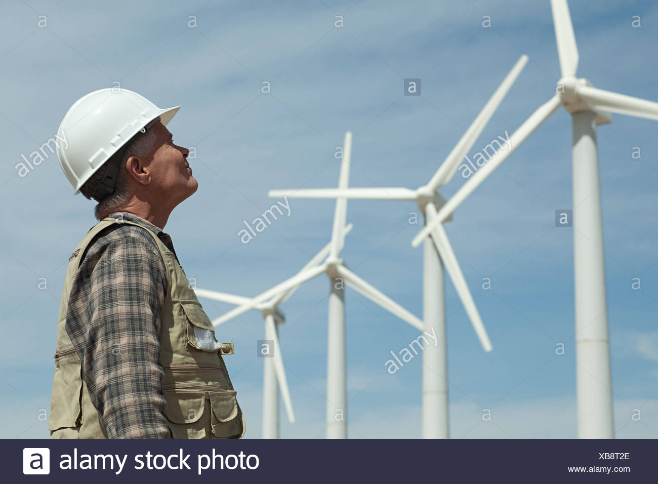 Man in hard hat looking at wind turbines Stock Photo