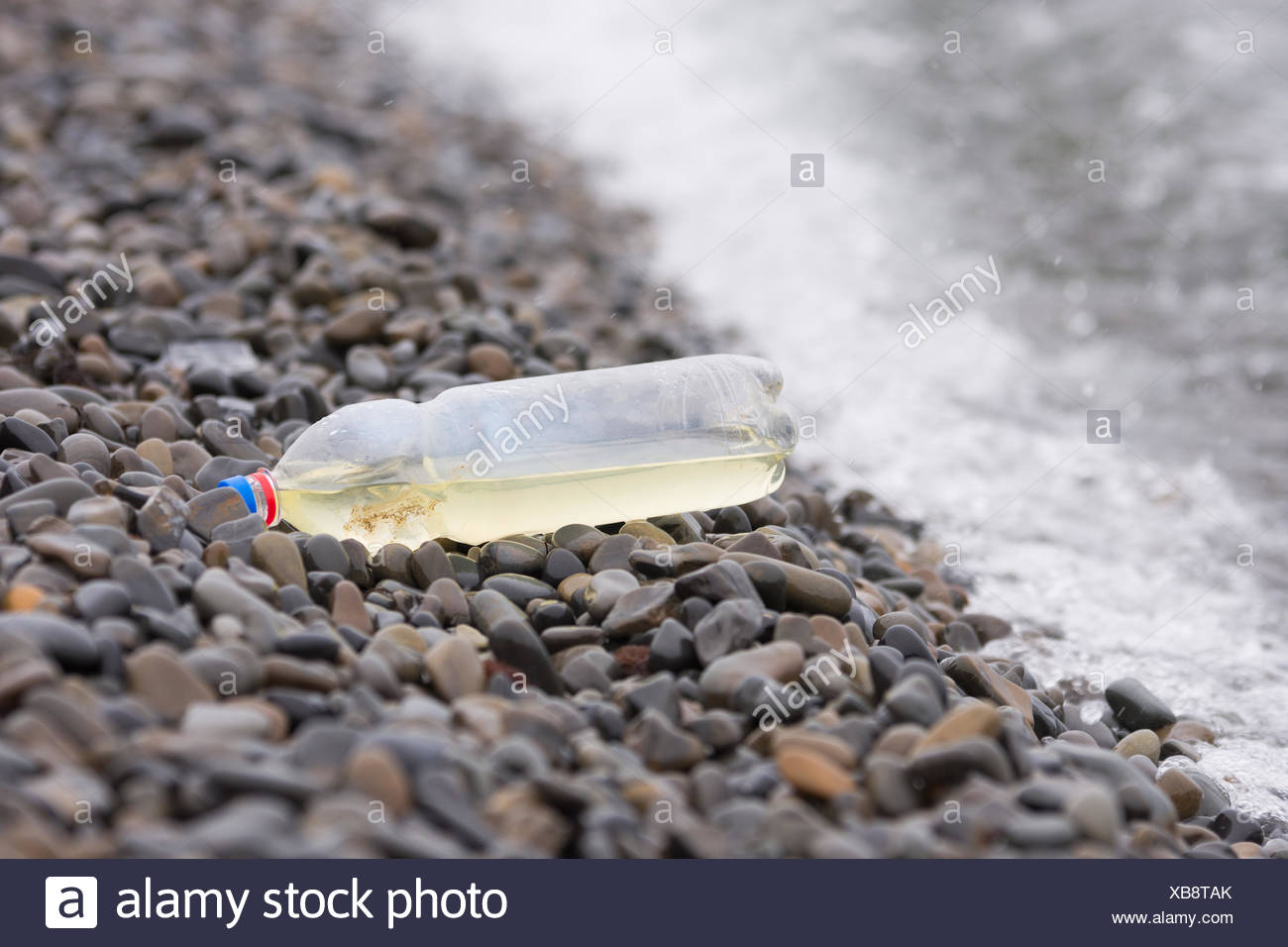 Plastic bottle lying on the pebbly seashore - Stock Image