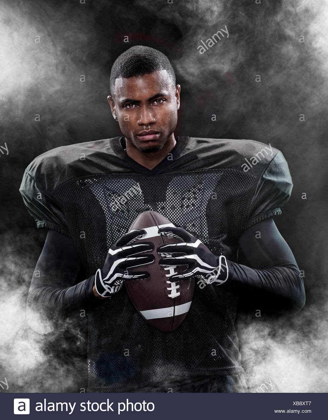 Portrait of an american football player surrounded by fog - Stock Image
