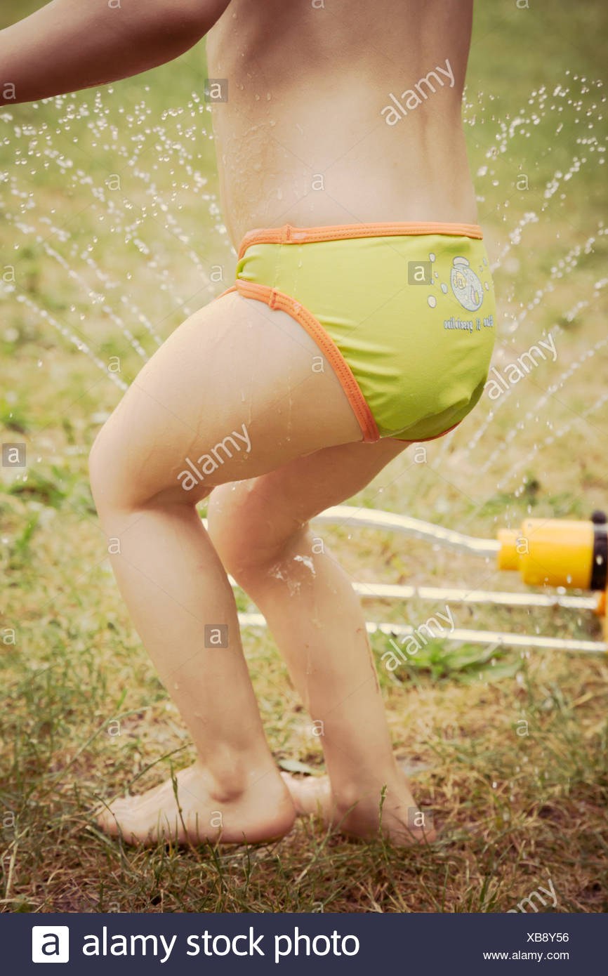 Lttle girl having fun with lawn sprinkler in the garten, partial view - Stock Image