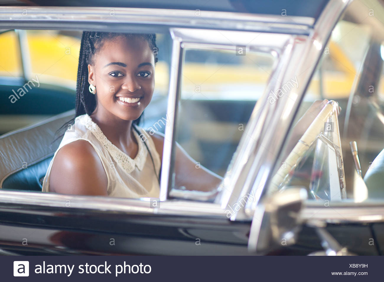 Woman in braided hairstyle driving vintage car - Stock Image