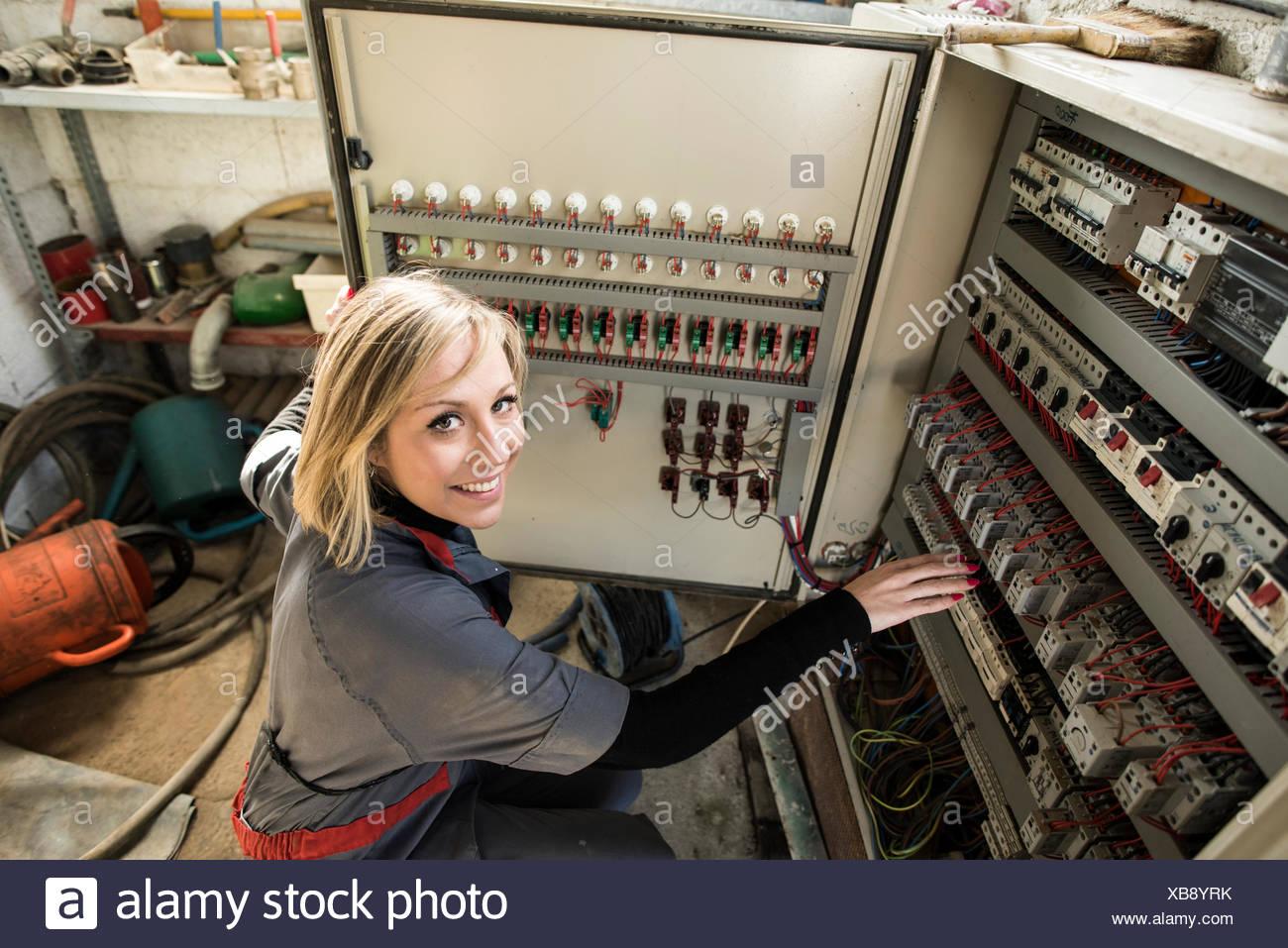 Woman checking fuse box - Stock Image