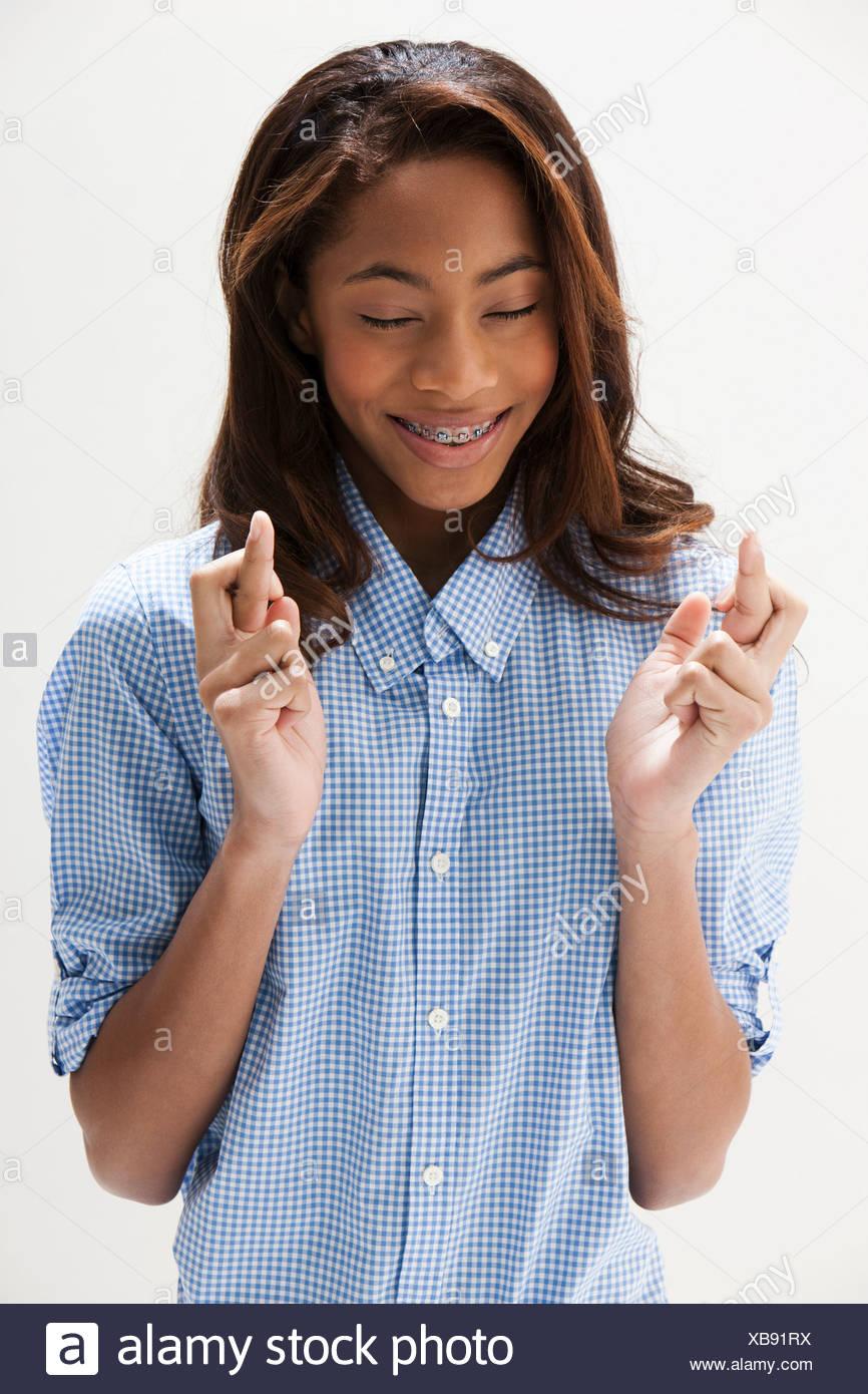 African American teenage girl with fingers crossed, studio shot - Stock Image